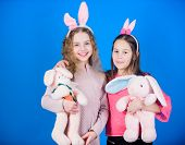 Friends Little Girls With Bunny Ears Celebrate Easter. Children With Bunny Toys On Blue Background.  poster