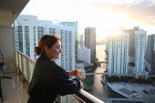 Woman In Bathrobe Drinking Her Morning Coffee Or Tea On A Downtown Balcony. Beautiful Sunrise In Dow poster