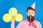 Man With Beard On Surprised Face Holds Air Balloons, Blue Background. Guy In Party Hat With Holiday  poster