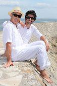 Volwassen vader en zoon zittend op een muur harbor