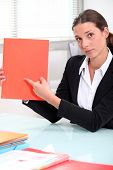 Brunette businesswoman pointing to a file left blank for your image