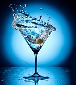 Splash martini from flying olives. Object on a blue background.