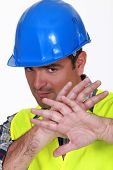 Tradesman holding his hands in front of his face