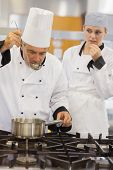 Teacher tasting his students soup with her watching anxiously in kitchen of culinary school