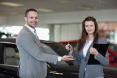Woman giving car keys to a man in a dealership