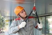 Worker builder doing facade works with Heavy Duty Lever Type Hand Rivet Tool