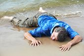 drowned dressed man lying on sea shore at tide
