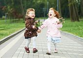 stock photo of little sister  - two happy little girls kids having fun while and laughing running in park racing against each other - JPG