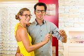 Junges Paar bei Optiker im Speicher, sie auf der Suche nach Brillen