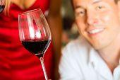Man testing wine in background wine barrels in wine cellar