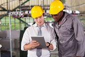 stock photo of overalls  - factory manager and worker looking at tablet computer - JPG