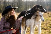 Lovely Blond Woman With Two Dogs In A Field