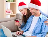 Online Christmas Shopping. Happy Smiling Couple Using Credit Card to Internet Shop. Young couple wit