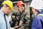 stock photo of forklift  - Portrait of happy young forklift driver with supervisor holding clipboard at warehouse - JPG