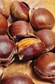 some roasted chestnuts, typical snack in All Saints Day in Spain, on a fall background with dry leaves