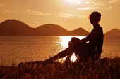 image of beach sunset  - A woman watching the sunset in the Caribbean - JPG