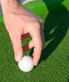 Man setting up a minigolf ball on a golf course