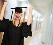 Happy Graduate Woman In Gown in a passageway of the university dorm