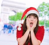 scared woman wearing a christmas hat against a street background