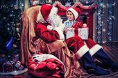 picture of nicholas  - Santa Claus giving a present to a little cute boy near the fireplace and Christmas tree at home - JPG