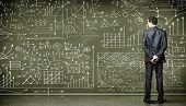 stock photo of clever  - Business person standing against the blackboard with a lot of data written on it - JPG