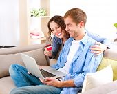 Online Shopping. Happy Smiling Couple Using Credit Card to Internet Shop. Young couple with laptop and credit card buying online. Christmas and New Year Gifts. e-shopping