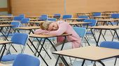 Woman leaning on desk napping in exam hall