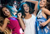 stock photo of party people  - Three glamorous girls enjoying themselves while dancing in night club - JPG