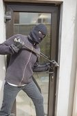 Burglar breaking into home using crow bar through back door