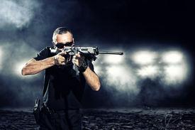foto of gunshot  - special  tactics man holding up his weapon - JPG