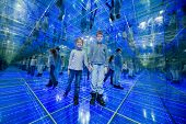Boy and girl standing in a mirrored room with blue lights holding hands