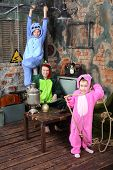 Family in colorful costumes of dragons pose in very old room with table and samovar.