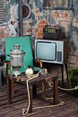 Old television, radio and wooden table with samovar in very old house.