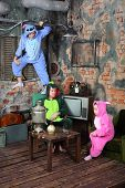 Family in colorful carnival costumes in very old room with television and table with samovar.