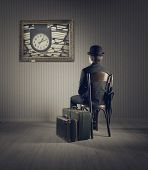 stock photo of bowler  - Business man sitting on old chair checking time for his travel - JPG
