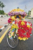 pic of malacca  - Trishaw Decorated with Colorful Silk Flowers Parked on Roadside in the Port Town of Malacca Malaysia - JPG