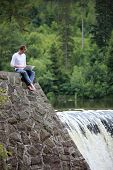 Man with notebook sitting at the bank of river over the waterfall