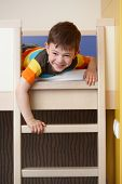 picture of bunk-bed  - Happy little boy having fun on bunk bed - JPG