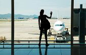Silhouette of young woman waiting for the flight