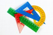 Protractor Ruler And Items For School And Education. On A Sheet In A Cage For Mathematics.