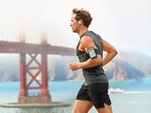 Running man - male runner in San Francisco listening to music on smart phone. Sporty fit young man j