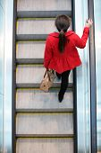 Urban people - woman commuter walking on escalator stairs in city. High angle view perspective from