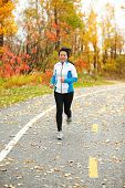 Middle aged woman running active in her 50s. Mature female jogging outdoor living healthy lifestyle in beautiful autumn city park in colorful fall foliage. Asian Chinese adult in her fifties.