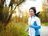 stock photo of mid autumn  - Active woman in her 50s running and jogging - JPG