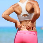 Back pain - woman having painful muscle injury in lower back. Fitness girl sport girl with sports in