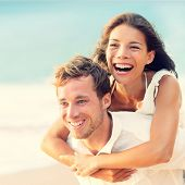 Love - Happy couple on beach having fun piggyback ride outdoor smiling happy laughing together on romantic holidays vacation travel trip. Young multiracial people, Asian woman, Caucasian man, 20s.
