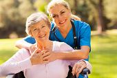 stock photo of disability  - happy senior woman in wheelchair outdoors with caring caregiver - JPG