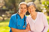 mid age medical nurse and senior patient outdoors