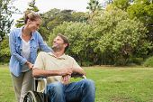 Smiling man in wheelchair talking with partner in the park on sunny day