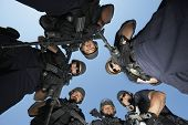 Low angle portrait of confident policemen with guns standing against sky